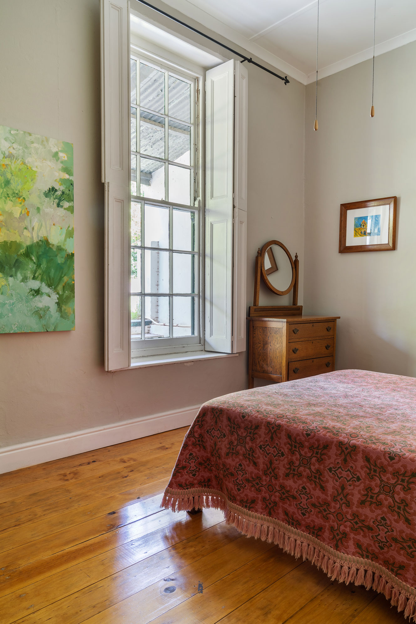 Pink and green bedroom with green art on the walls