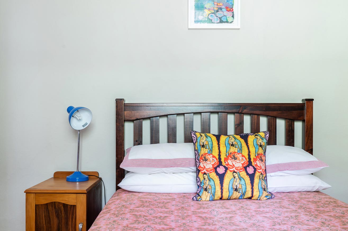 Pink and green bedroom with a mix of bold patterns and graphic, illustrative fabrics