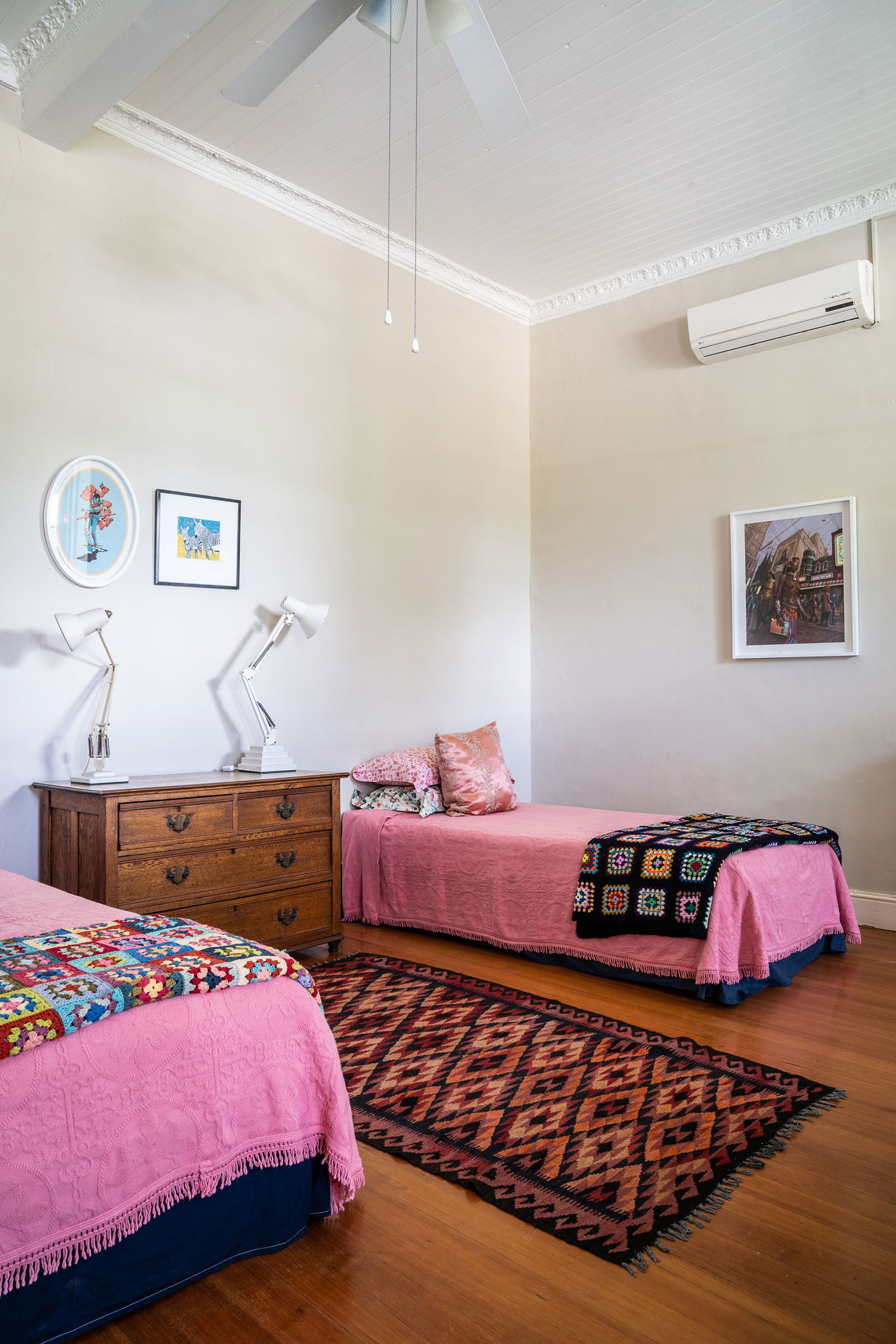 Pink bedroom with antique dresser and bold patterns and colours