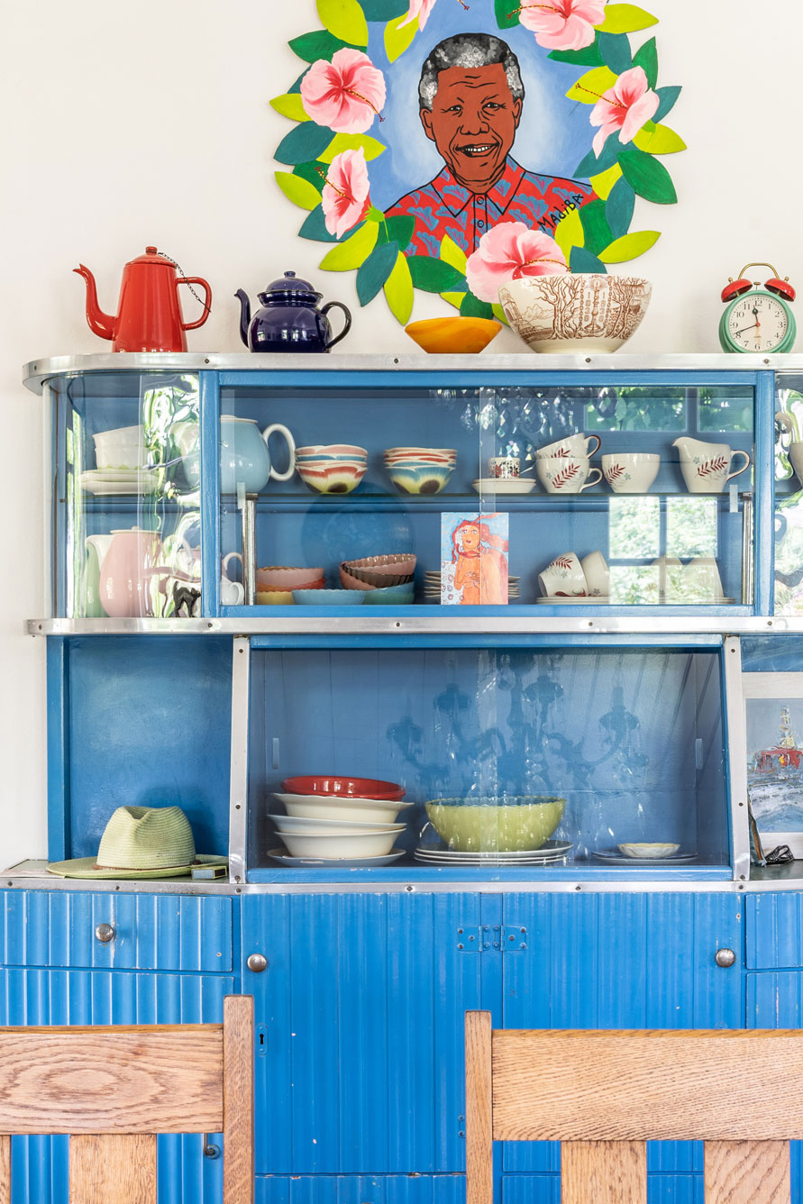 A blue vintage cabinet styled with colourful trinkets and South African paraphernalia